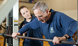 Changing Aging: Senior Man Exercising with Trainer